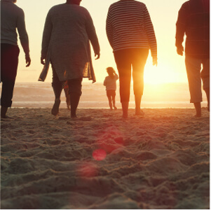 Full length shot of a senior group of friends enjoying a day on the beach with their grandchildren at sunset